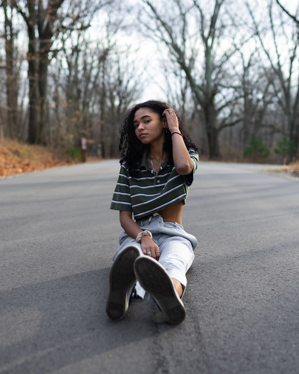 woman in black and white stripe shirt and blue denim jeans sitting on road during daytime
