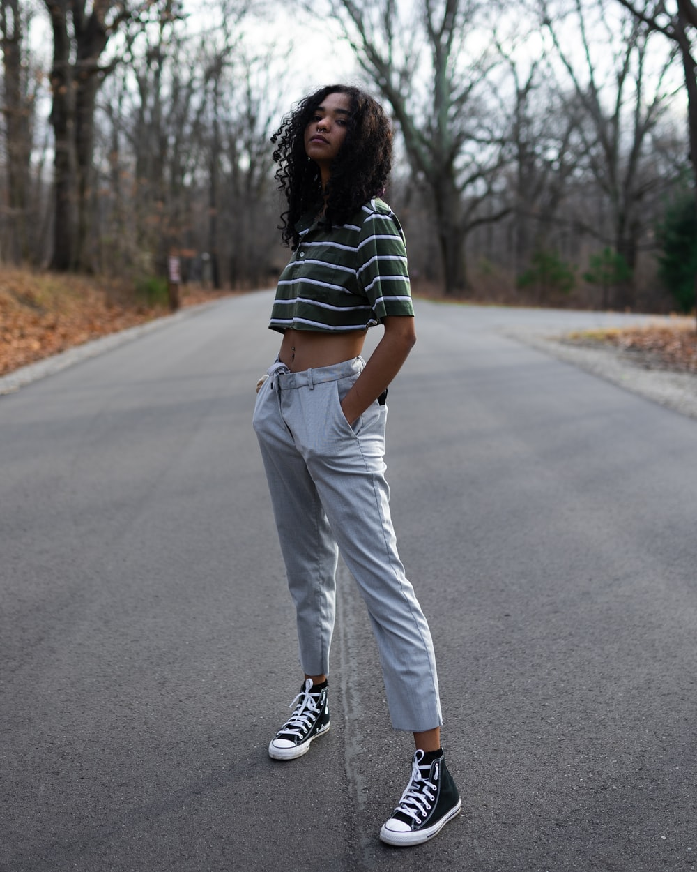 woman in black and white stripe shirt and white pants walking on road during daytime