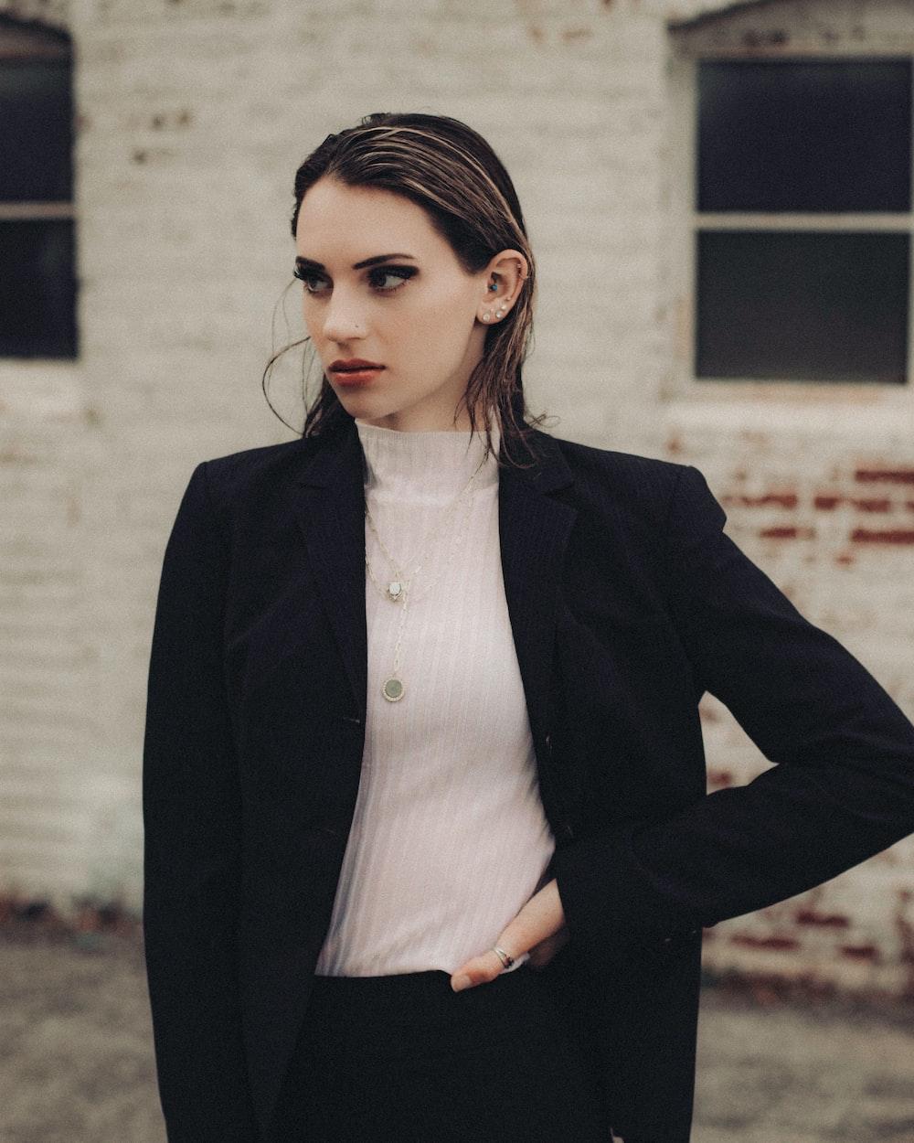 woman in black blazer standing near white wall