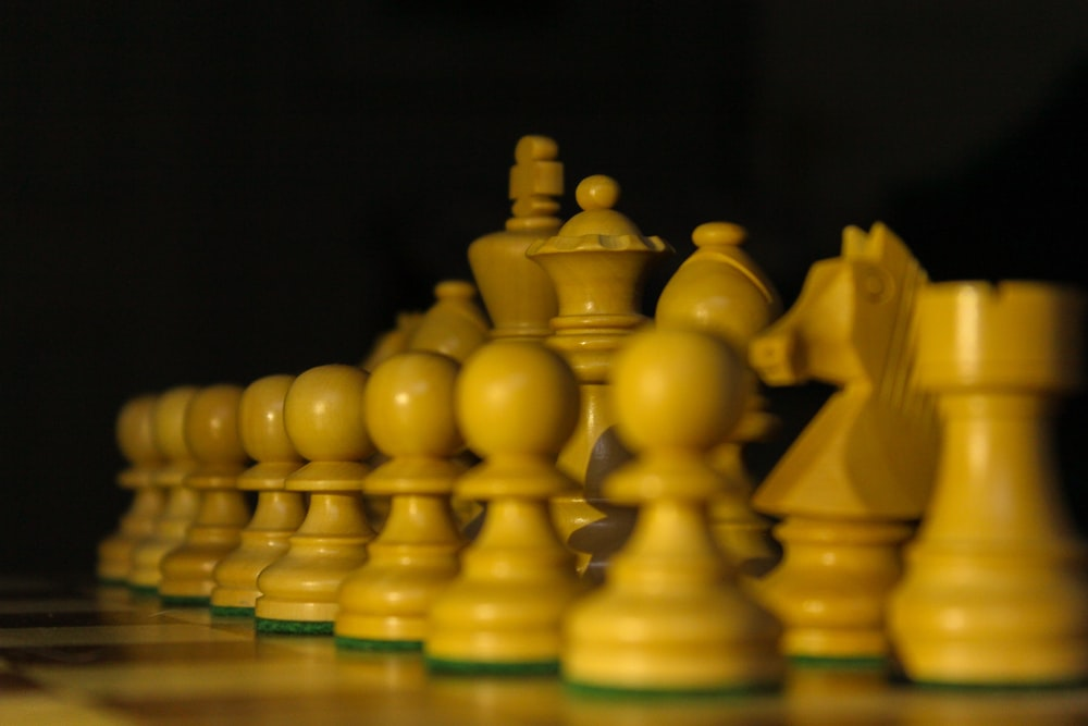 yellow chess pieces on blue table