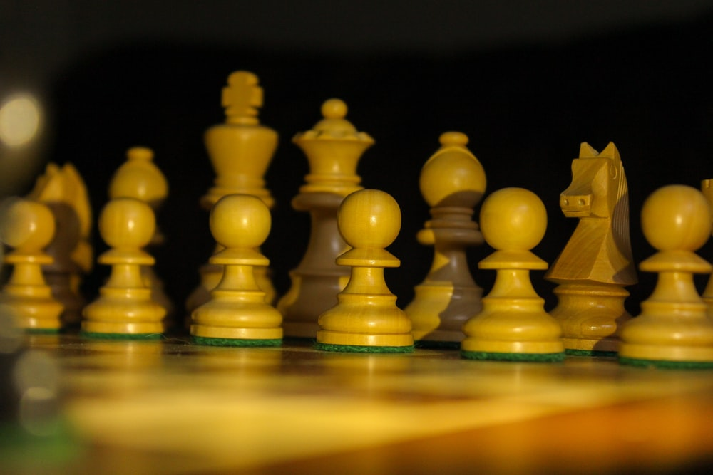 yellow chess pieces on brown wooden chess piece