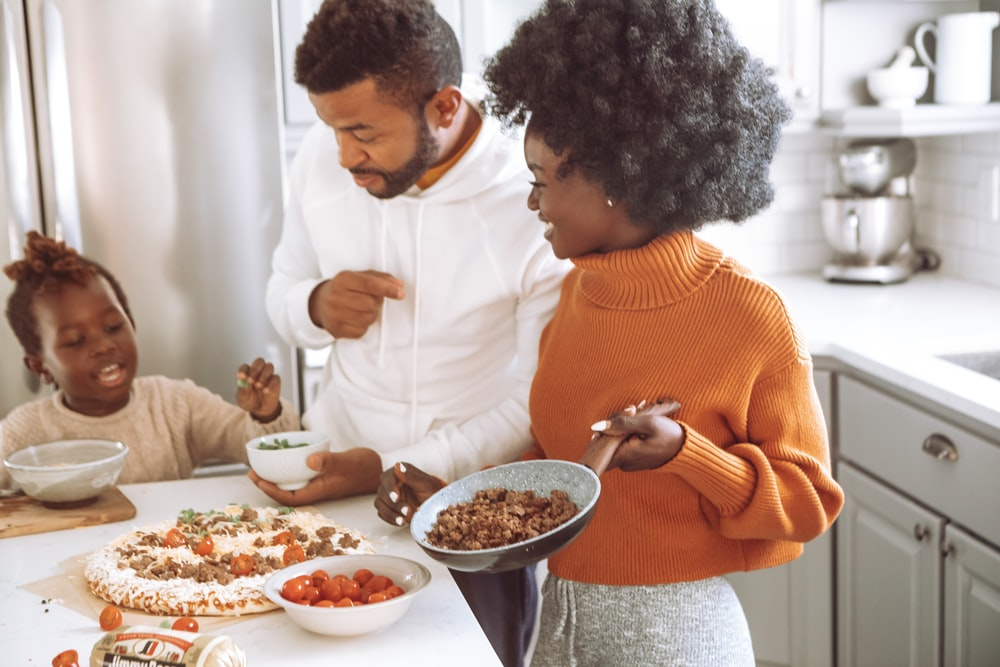 woman in orange sweater holding white ceramic bowl with food