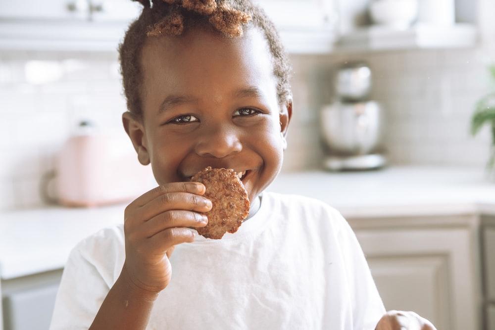 girl in white shirt holding brown bread
