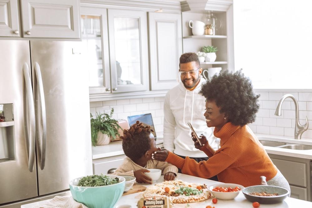 man in orange dress shirt sitting beside woman in white long sleeve shirt
