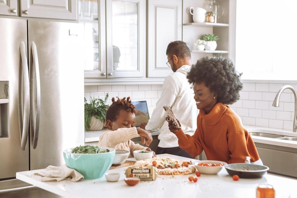 man in white dress shirt sitting beside woman in orange long sleeve shirt eating