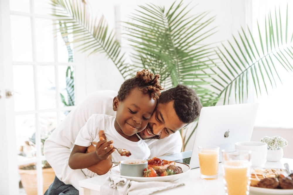 man in white dress shirt eating beside woman in white long sleeve shirt