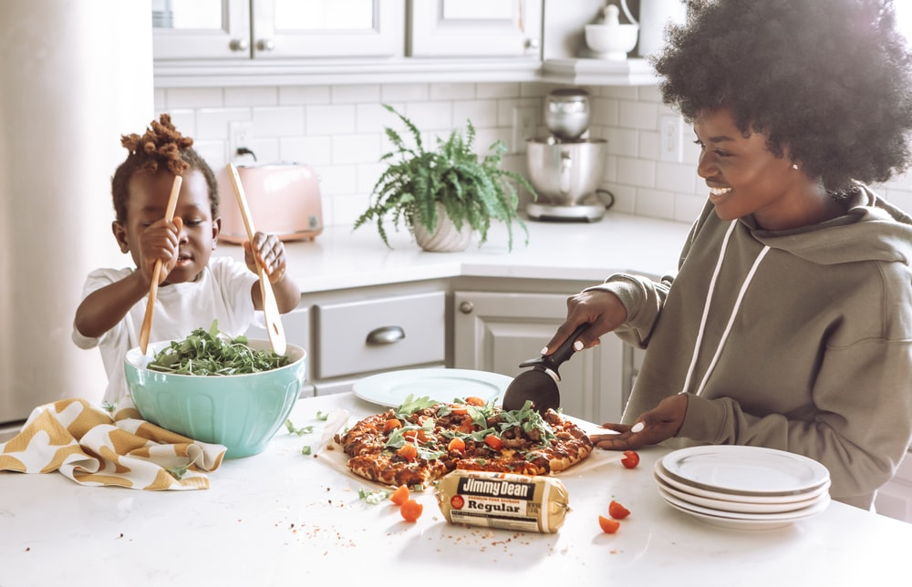 woman in white long sleeve shirt slicing pizza