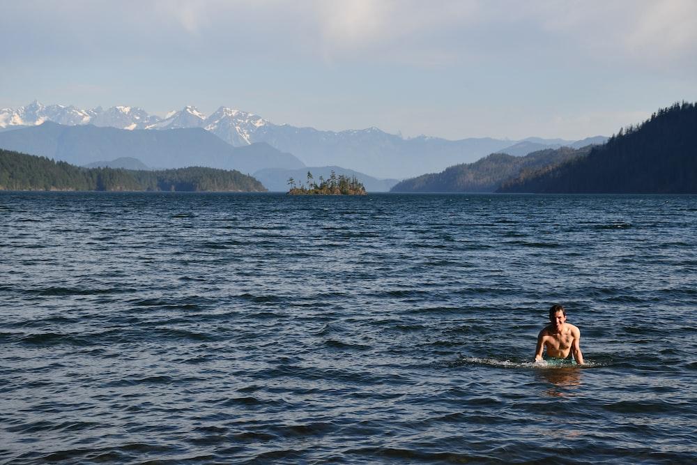 woman in black bikini on body of water during daytime