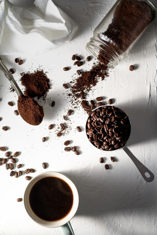 coffee beans on white ceramic mug beside stainless steel spoon