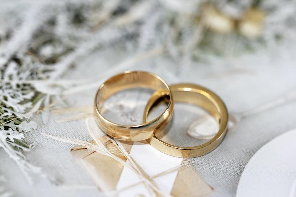золотое обручальное кольцо на белой ткани