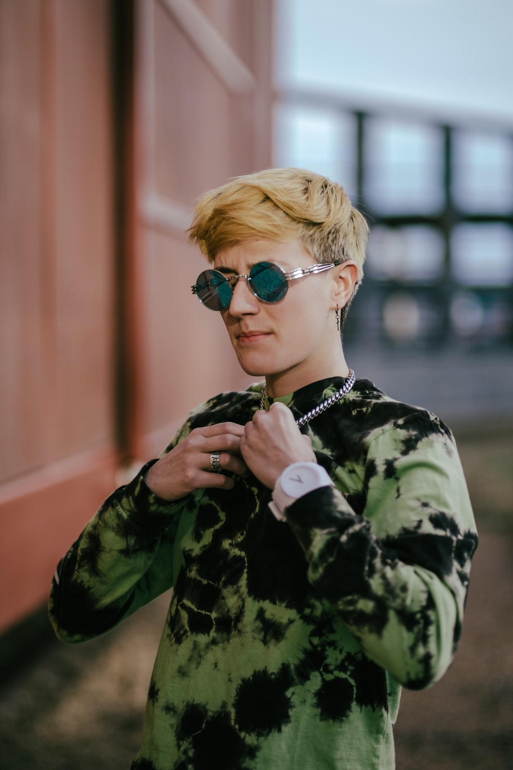 boy in green and black camouflage jacket wearing blue sunglasses