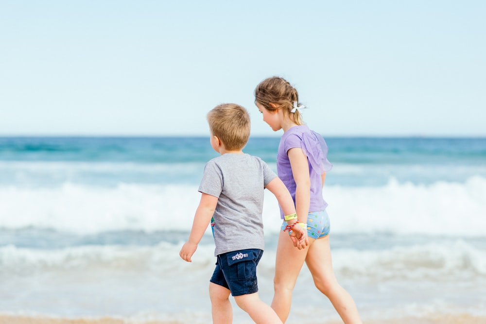 boy in white t-shirt and blue shorts standing on seashore during daytime