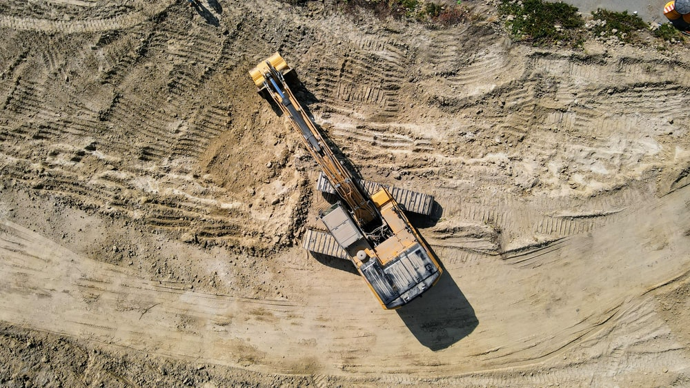 black and yellow heavy equipment on brown rock formation during daytime