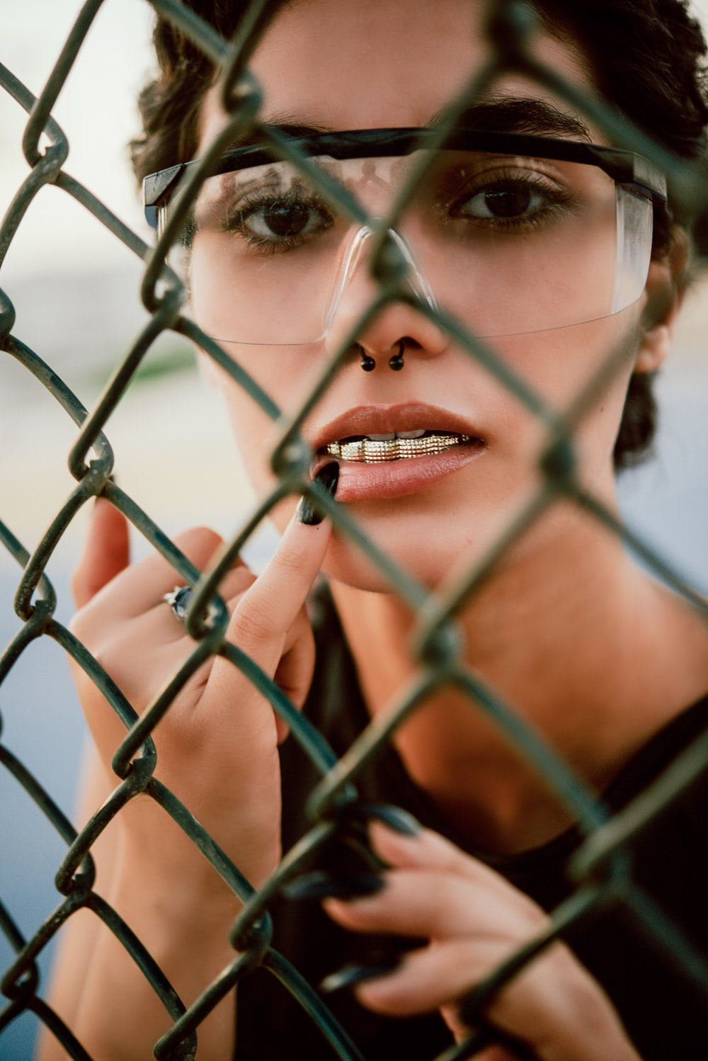 woman in red lipstick behind gray metal fence