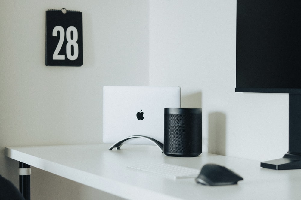 silver imac beside black and silver corded computer mouse on white wooden desk