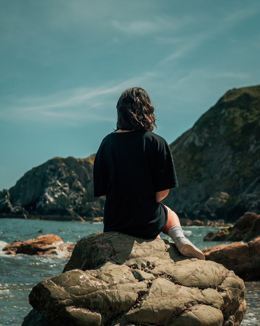 woman in black shirt sitting on rock near body of water during daytime