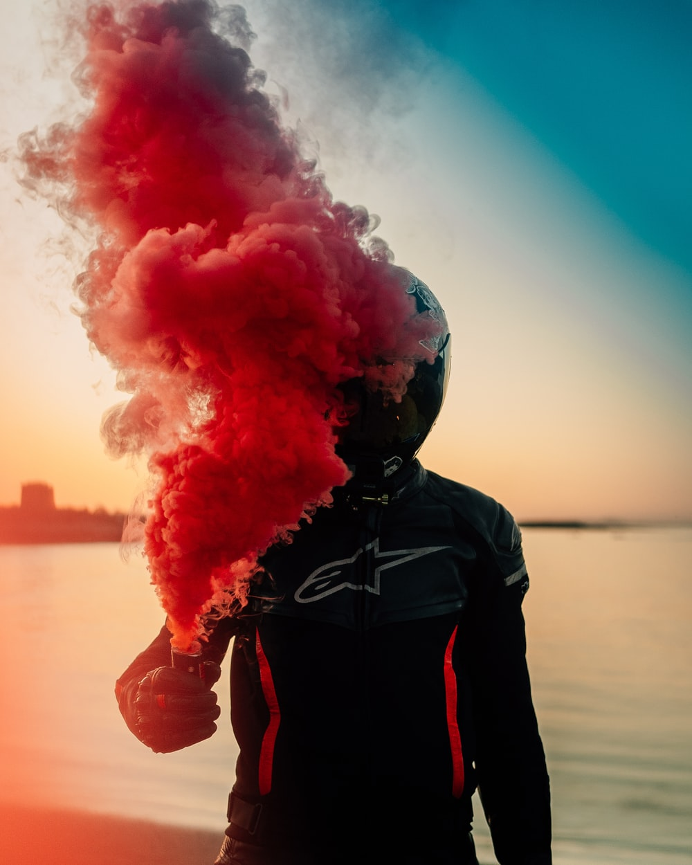 person in black hoodie with red smoke on his face