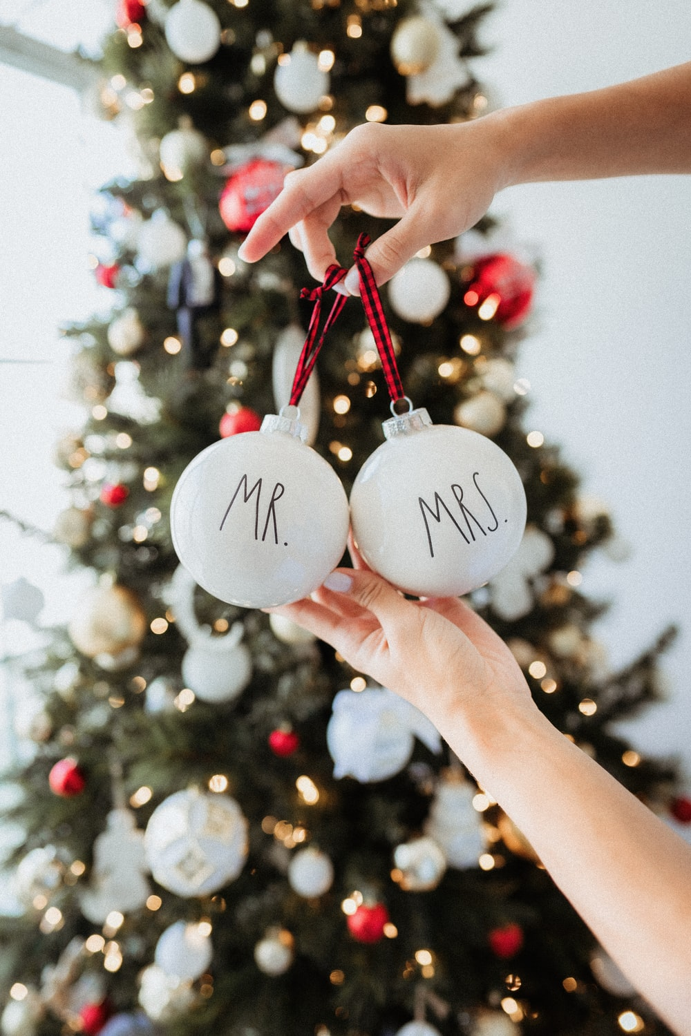 person holding white and red christmas baubles