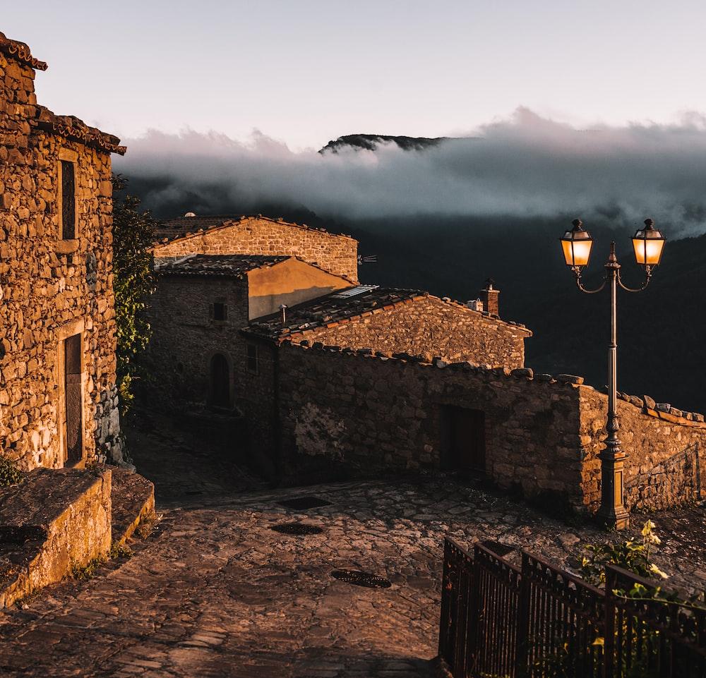 brown brick building near mountain under white clouds during daytime