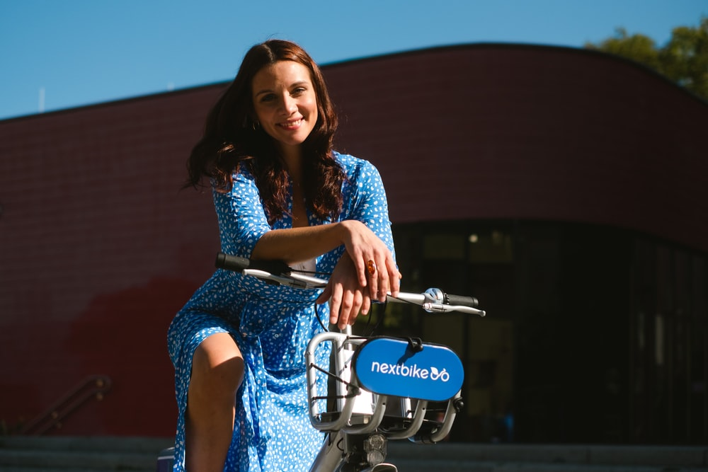 woman in blue and white floral dress riding on motorcycle