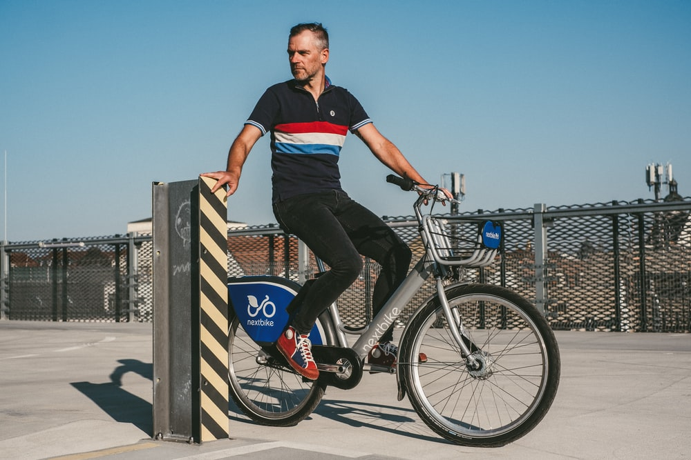 man in black t-shirt and black denim jeans riding on bicycle