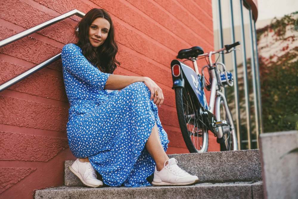 woman in blue and white polka dot dress sitting on white metal railings