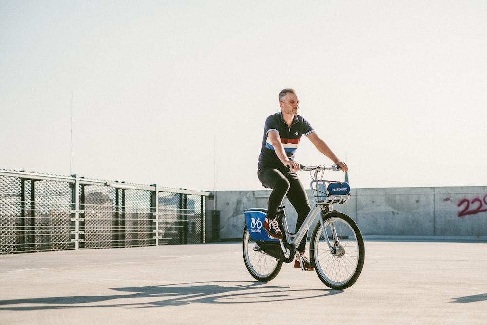 man in black tank top riding on bicycle during daytime
