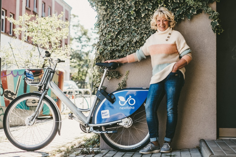 woman in white long sleeve shirt and blue denim jeans standing beside blue bicycle during daytime