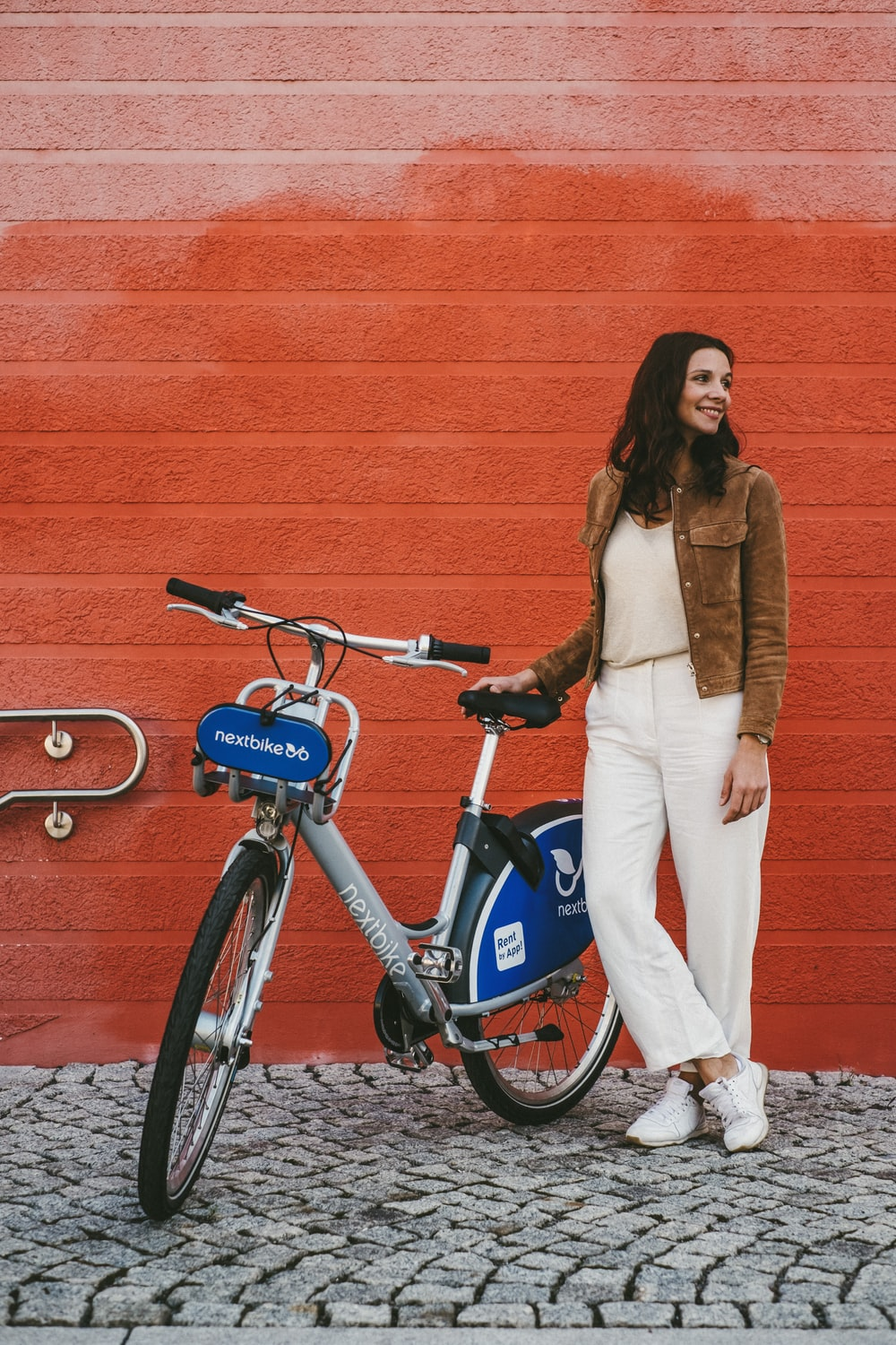 woman in brown coat and white pants standing beside blue and black bicycle