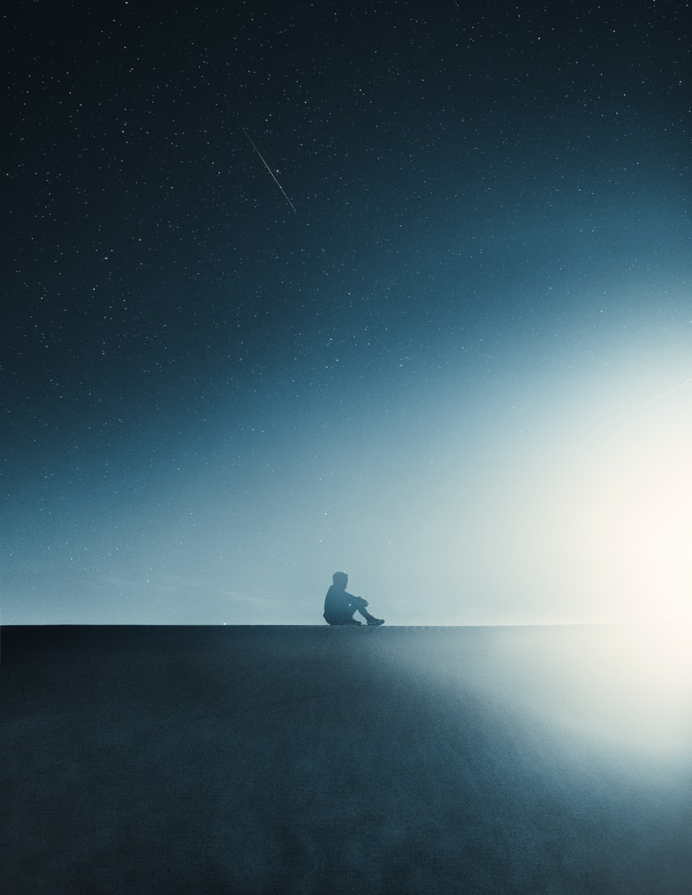 silhouette of person sitting on rock under starry night