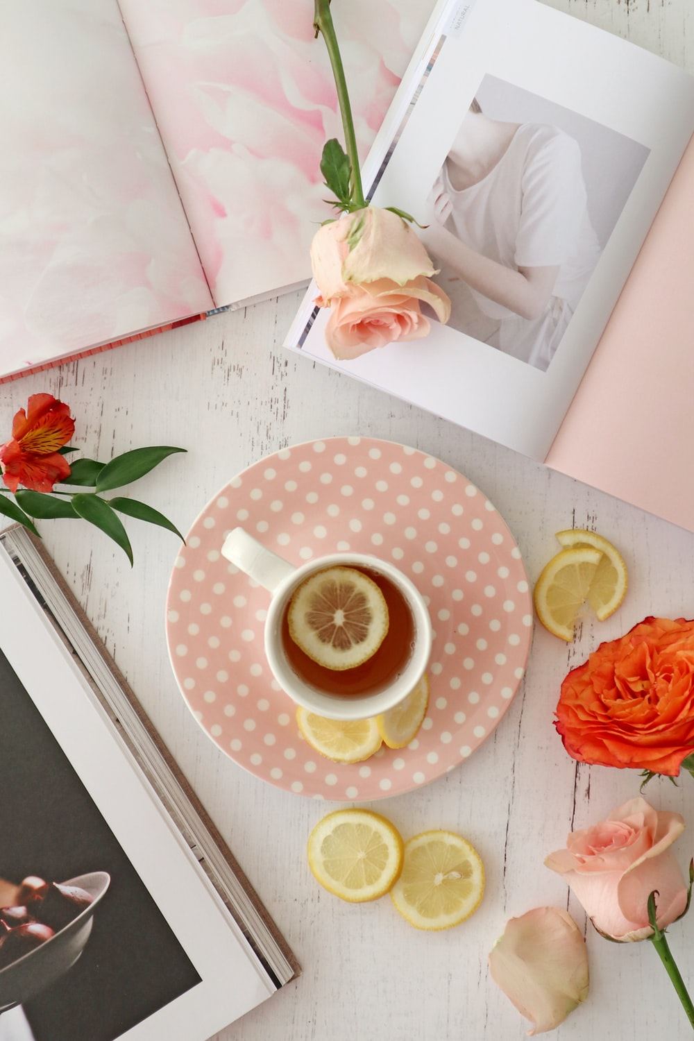 pink rose beside yellow and white polka dot ceramic cup with saucer