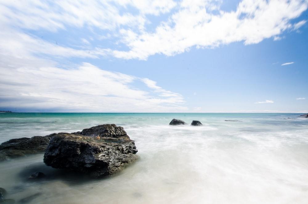black rock formation on sea under blue sky during daytime