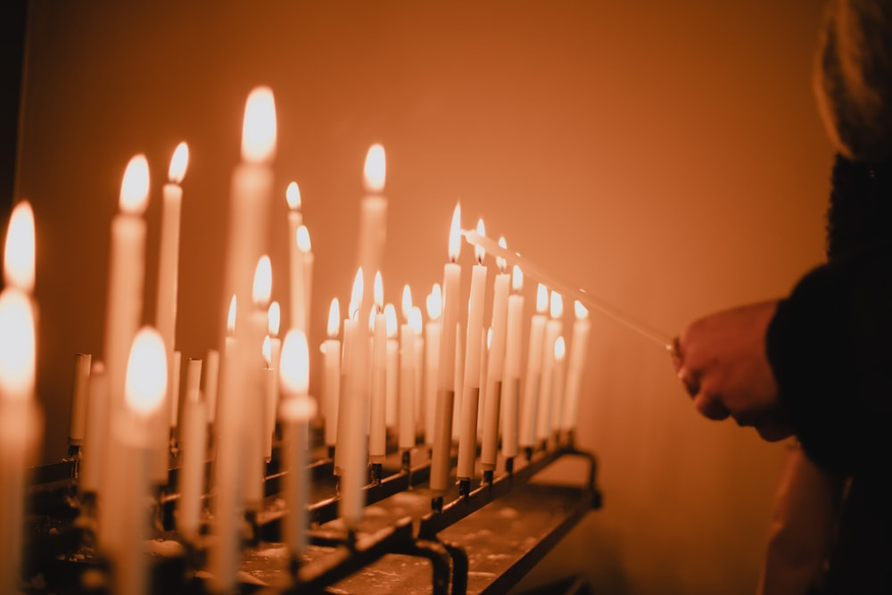 man standing near lighted candles