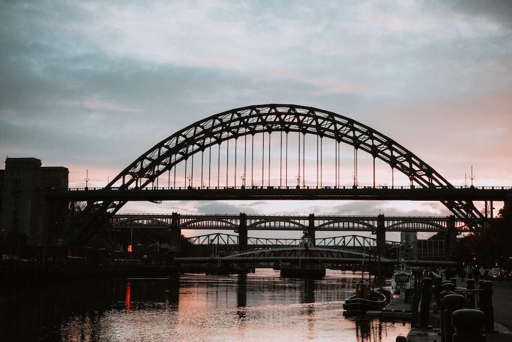 black metal bridge over body of water during daytime