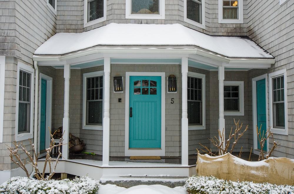 blue wooden door on white wooden house
