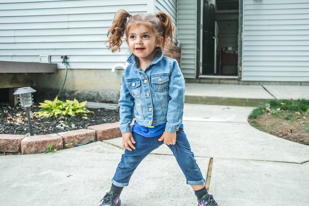 girl in blue denim jacket and blue denim jeans standing on gray concrete floor during daytime
