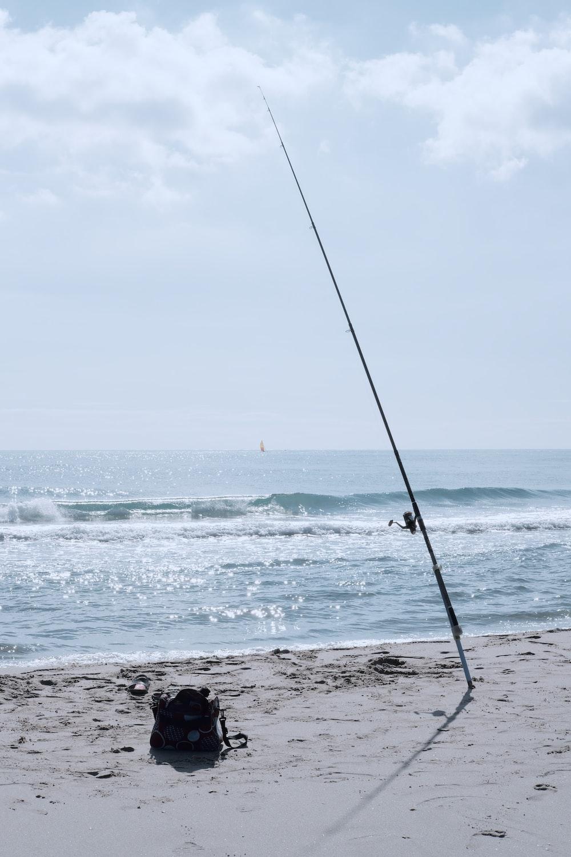 black fishing rod on seashore during daytime