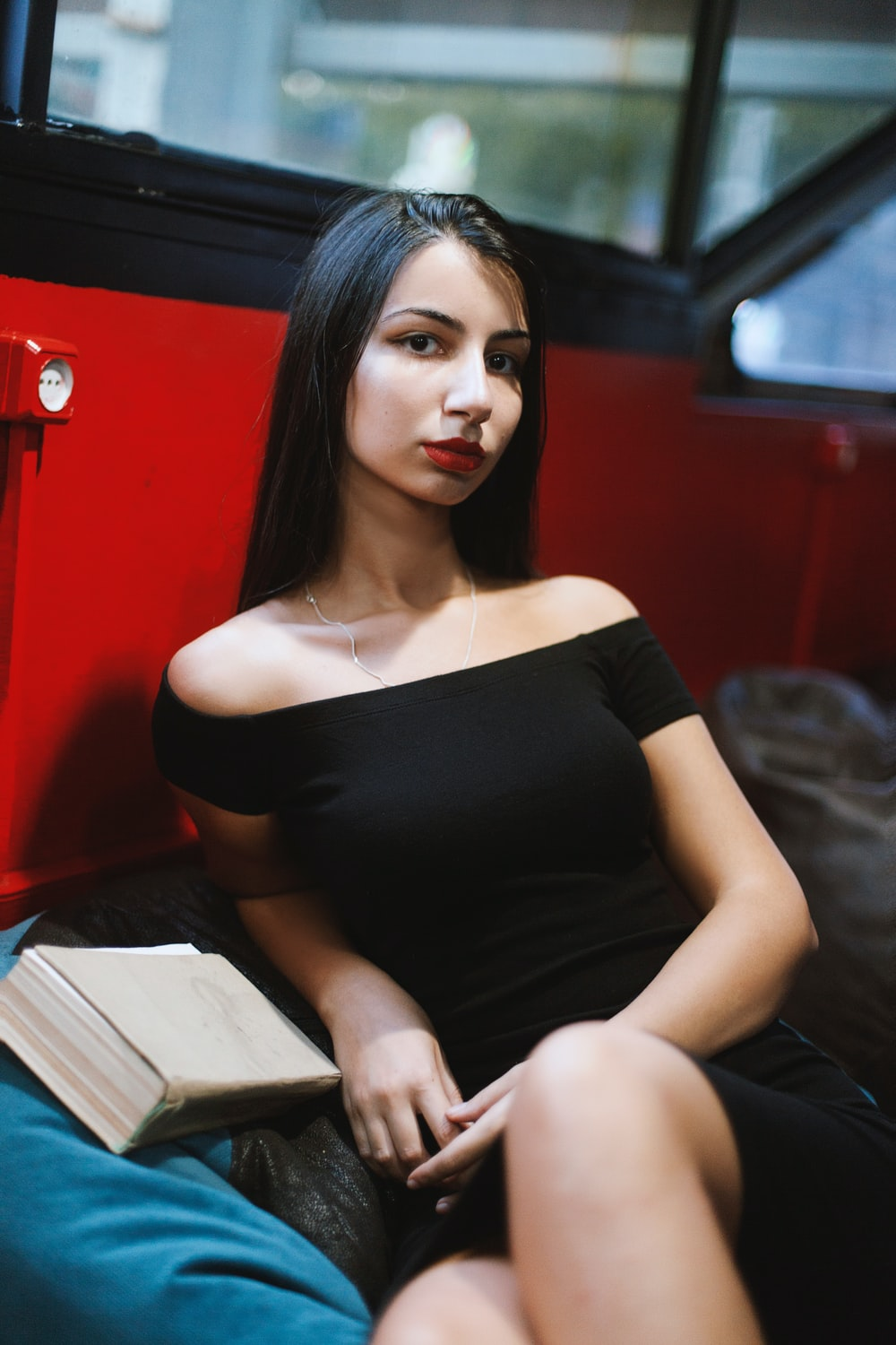 woman in black tube dress sitting on gray couch