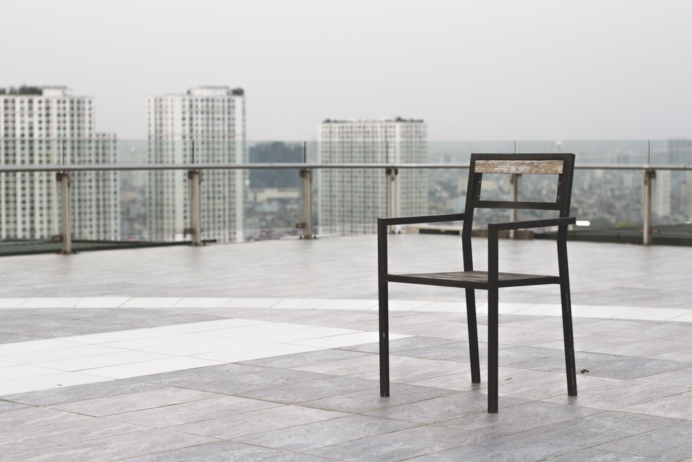 black wooden table and chairs on white floor tiles
