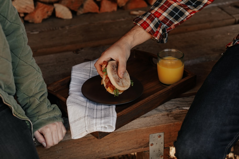 person holding burger on black plate