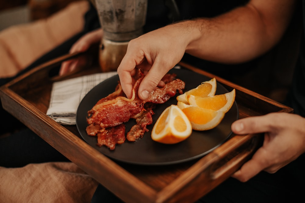 person slicing raw meat on black plate