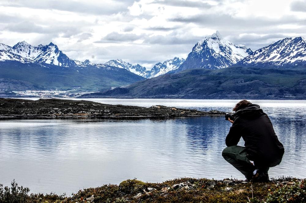 man in black jacket and blue denim jeans sitting on rock near lake during daytime