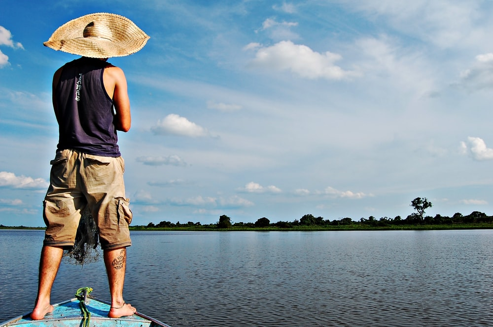man in blue tank top and brown shorts standing on green boat on lake during daytime