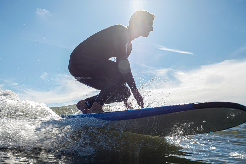 man in black wetsuit surfing on water during daytime