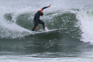 man in black wet suit surfing on water during daytime