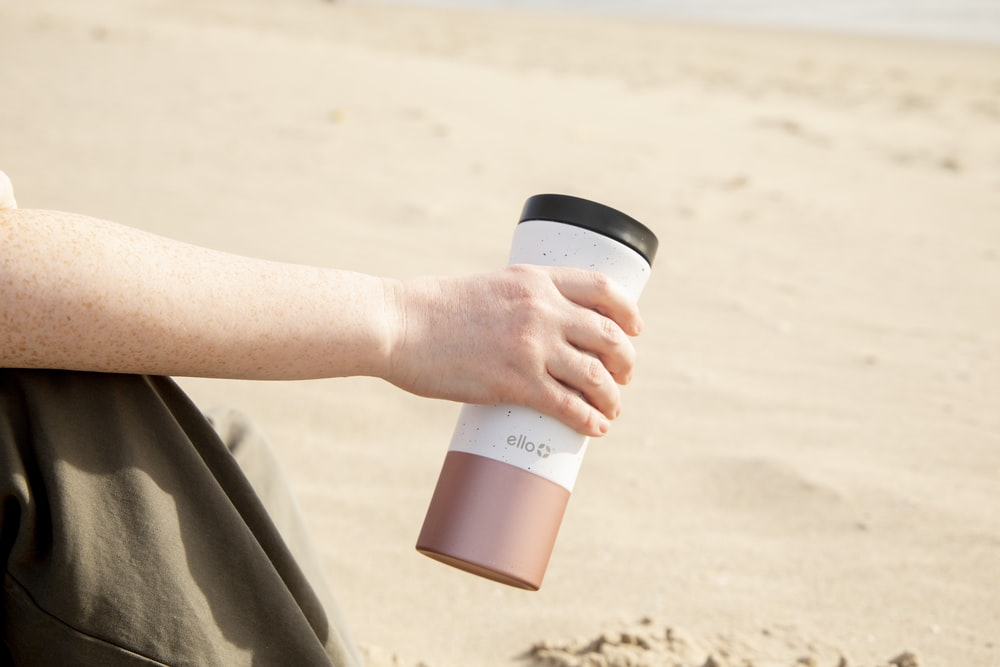 person holding white and black plastic cup