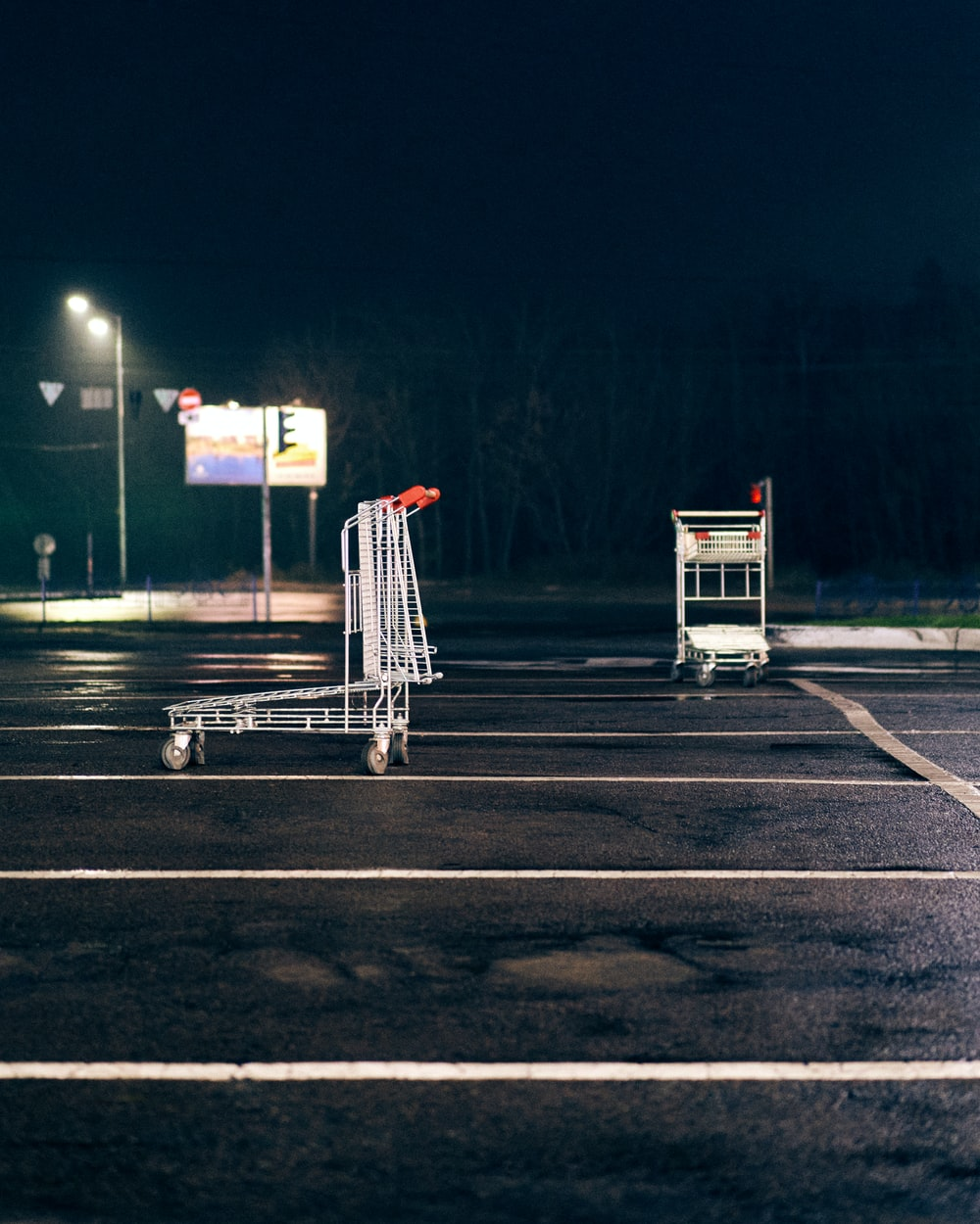 white and red metal cart on gray concrete road during night time