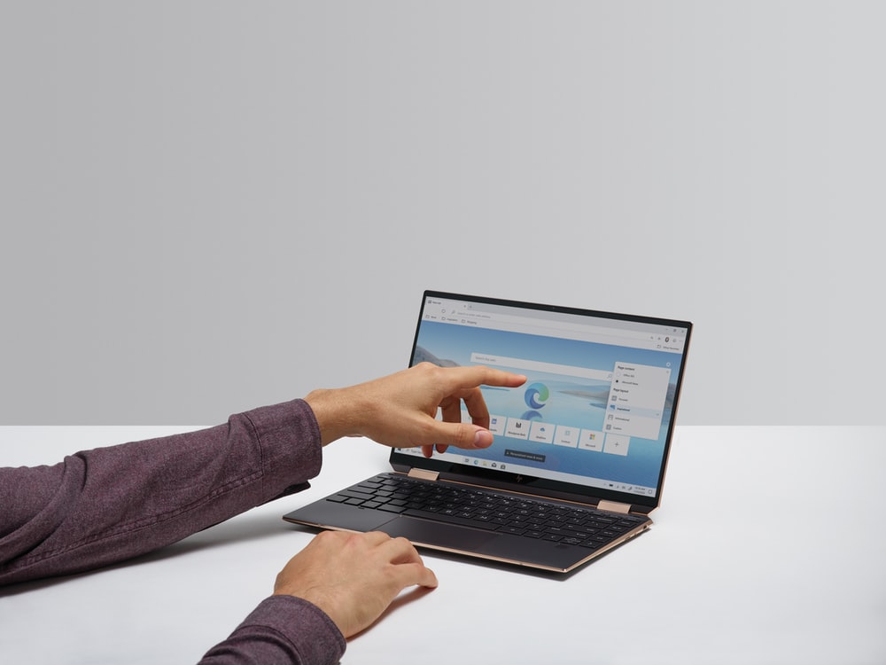 person in gray long sleeve shirt using black laptop computer