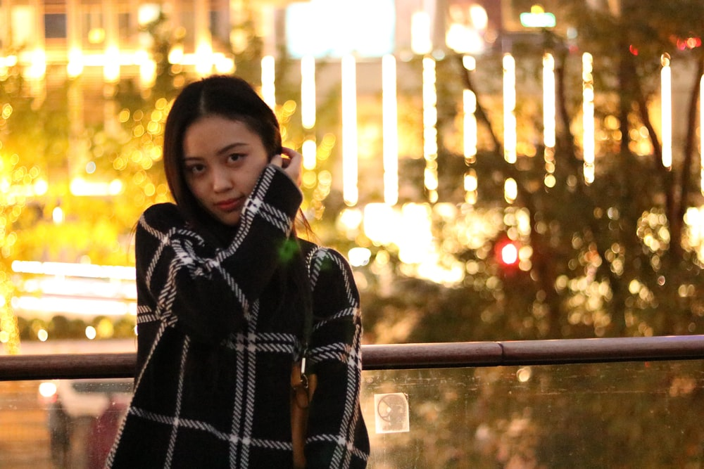 woman in black and white plaid coat standing near railings during night time