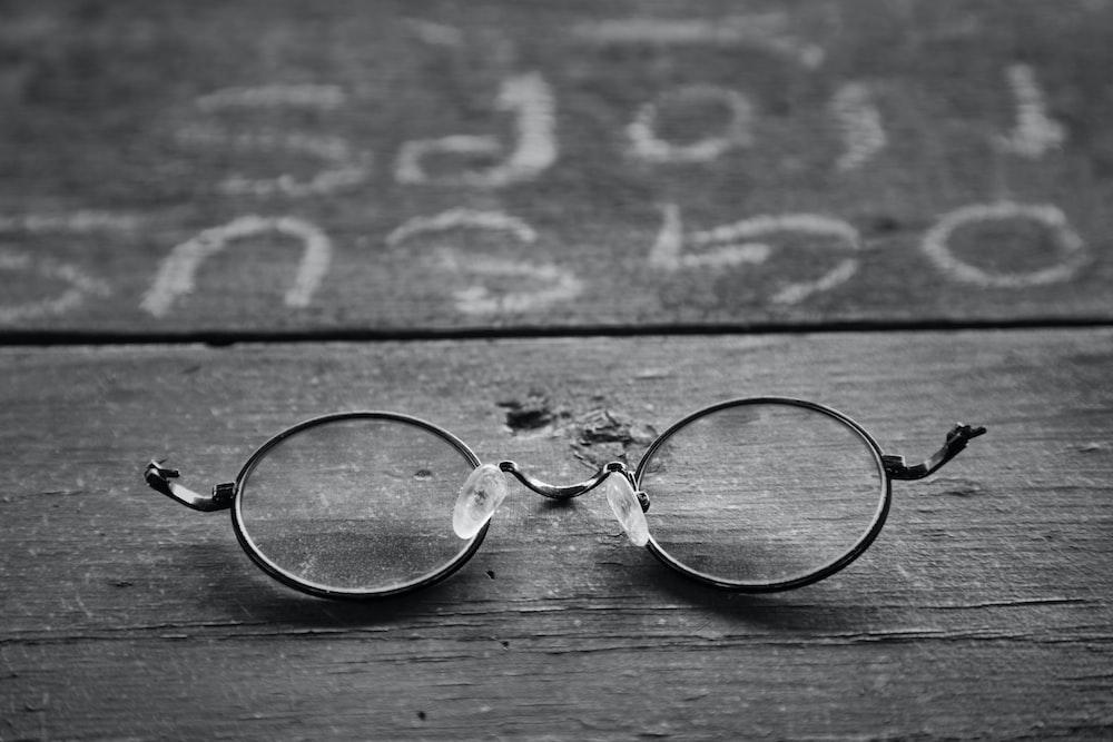 silver framed eyeglasses on wooden surface